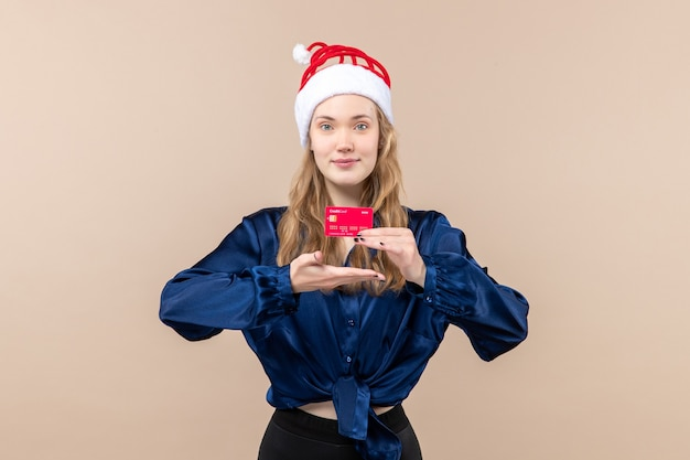 Front view young female holding red bank card on a pink background holiday photo new year emotion christmas money