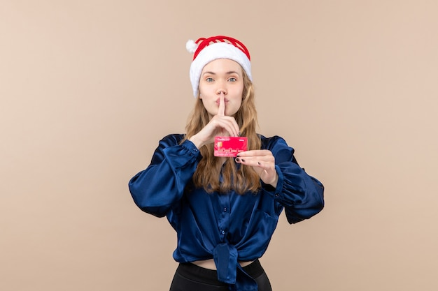 Front view young female holding red bank card on a pink background holiday photo new year xmas money emotion