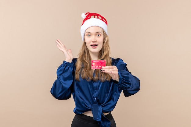 Front view young female holding red bank card on pink background holiday photo new year xmas money emotion