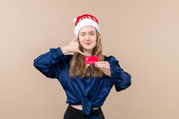 Front view young female holding red bank card on the pink background holiday photo new year xmas money emotion