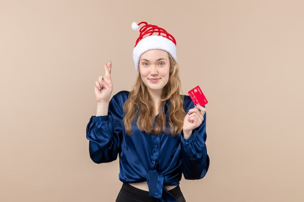 Front view young female holding red bank card on pink background holiday xmas money photo new year emotion