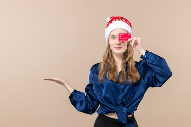 Front view young female holding red bank card on pink background holiday xmas money photo new year emotions