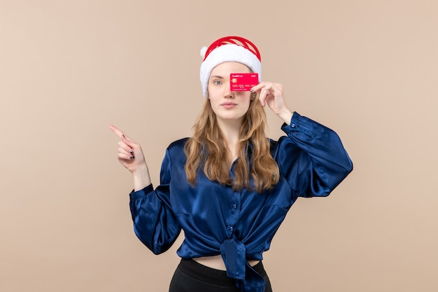 Front view young female holding red bank card on pink background holiday xmas money photos new year emotion