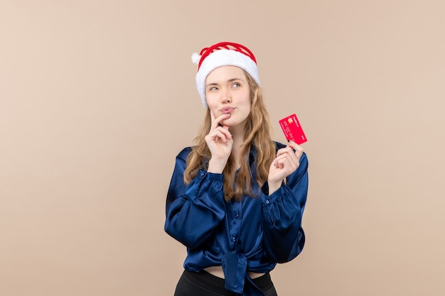 Front view young female holding red bank card on a pink background money holiday new year xmas photo emotion free place