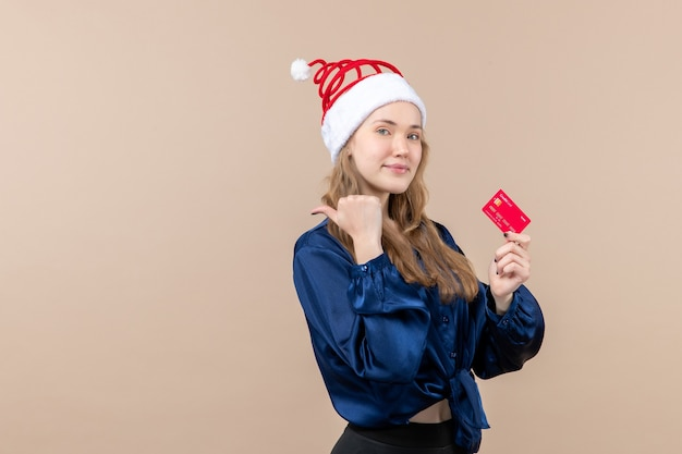 Front view young female holding red bank card on pink background money holiday new year xmas photo emotion free place