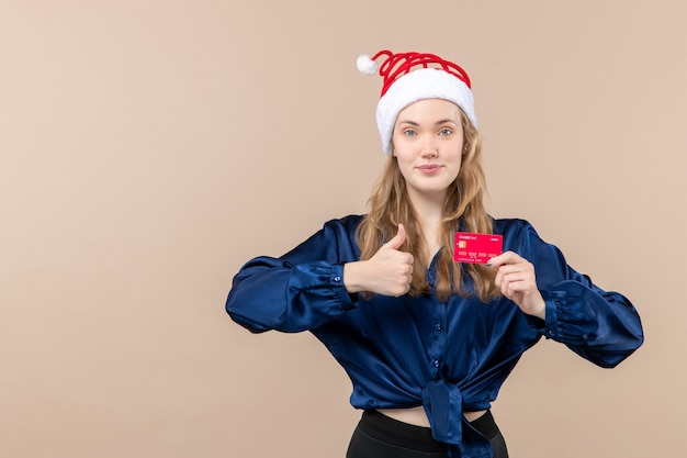 Front view young female holding red bank card on pink background money holidays photo new year xmas emotion free place