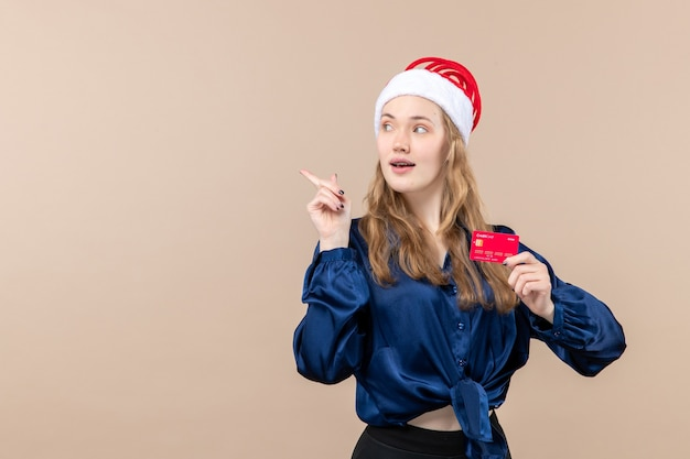 Front view young female holding red bank card on pink background money holidays photo new year xmas emotions free place