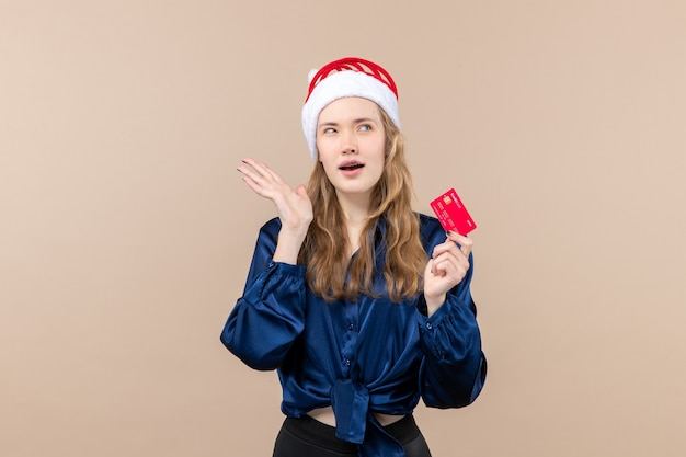 Front view young female holding red bank card on a pink background money photo holiday new year xmas emotion