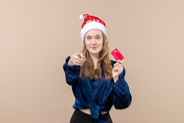 Front view young female holding red bank card on pink background money photo holiday new year xmas emotion