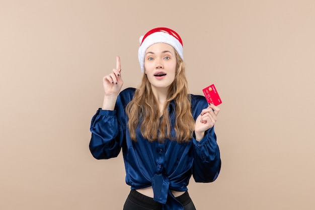 Front view young female holding red bank card on the pink background xmas money photo holiday new year emotion