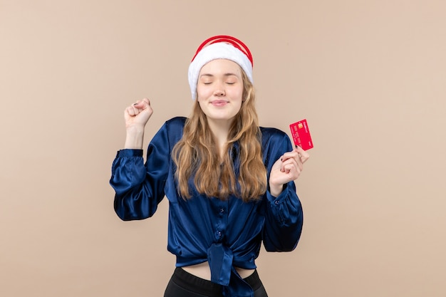 Front view young female holding red bank card on pink background xmas money photo holiday new year emotions