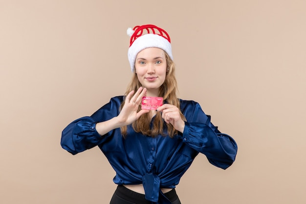 Front view young female holding red bank card on pink desk holiday xmas money photo new year emotion