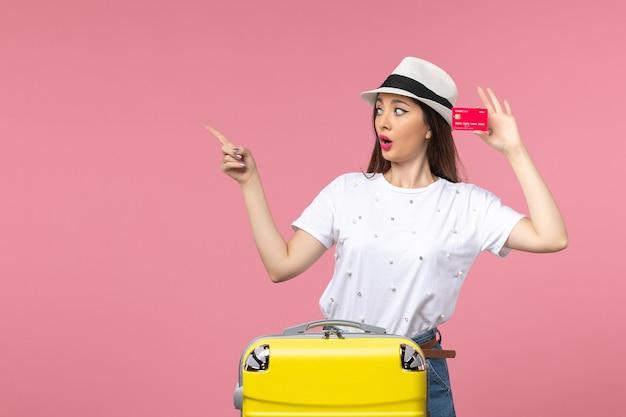 Vista frontale giovane donna che tiene carta di credito rossa sulla parete rosa viaggio estivo colori