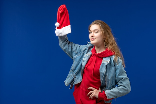 Front view young female holding red christmas cap on blue background emotion christmas color
