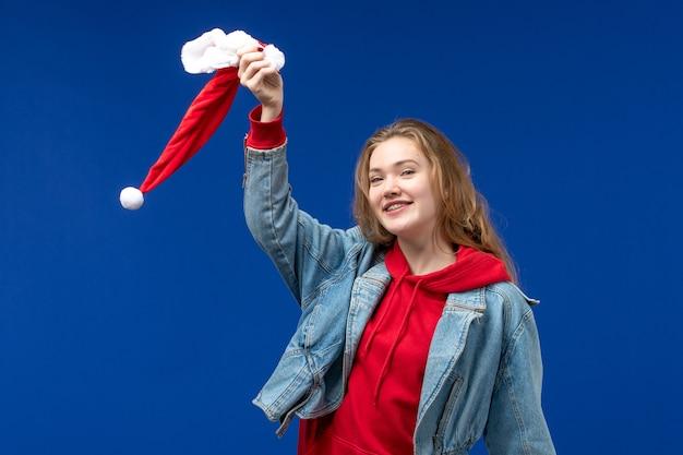 Вид спереди молодая женщина держит красную рождественскую шапку на синем фоне эмоции рождественского цвета