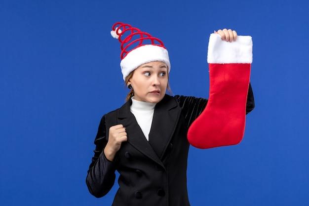 Giovane femmina di vista frontale che tiene il calzino rosso di natale sull'essere umano del nuovo anno di festa della parete blu