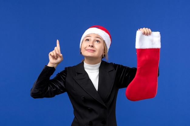 Giovane femmina di vista frontale che tiene il calzino rosso di natale sul nuovo anno di festa umana della parete blu