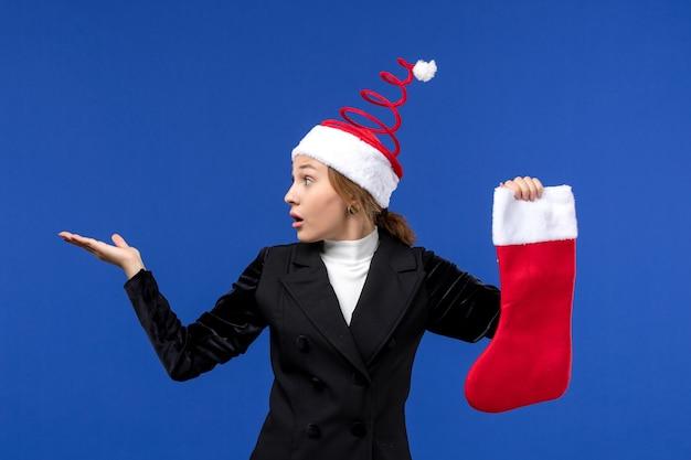 Giovane femmina di vista frontale che tiene il calzino rosso di natale sulla festa umana del nuovo anno della parete blu
