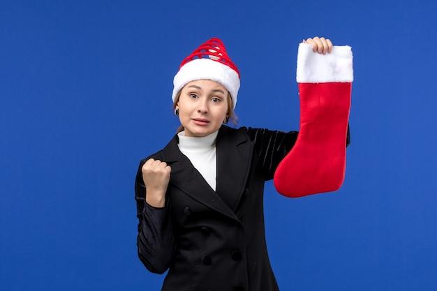 Вид спереди молодая женщина, держащая красный рождественский носок на синем столе, праздник нового года человека