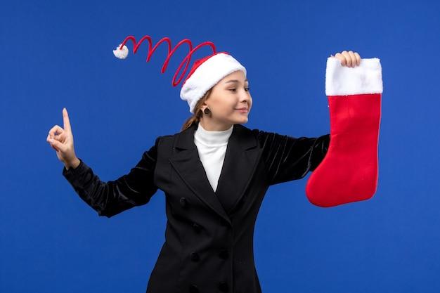 Вид спереди молодая женщина, держащая красный рождественский носок на синем столе, праздник человека, новый год