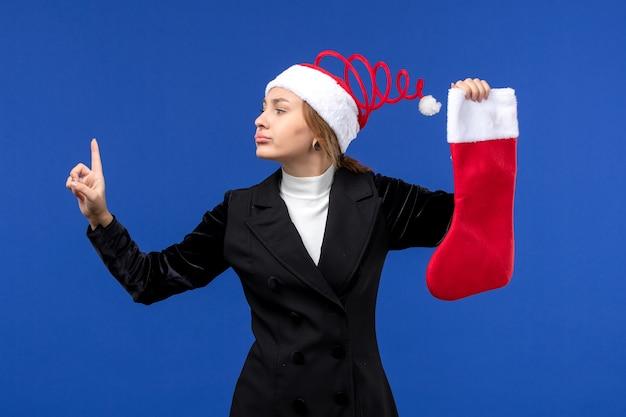 Вид спереди молодая женщина держит красный рождественский носок на синем столе человеческие праздники новый год