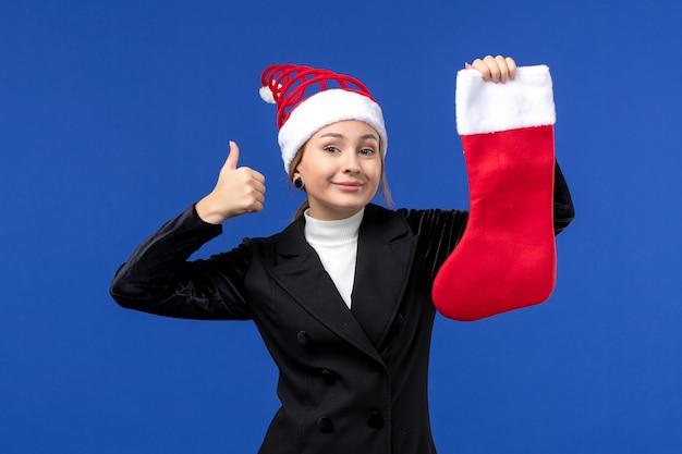 青い壁の休日の新年の人間に赤いクリスマス靴下を保持している正面図若い女性