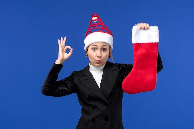 青い壁の休日の新年の人間に赤いクリスマス靴下を保持している正面図
