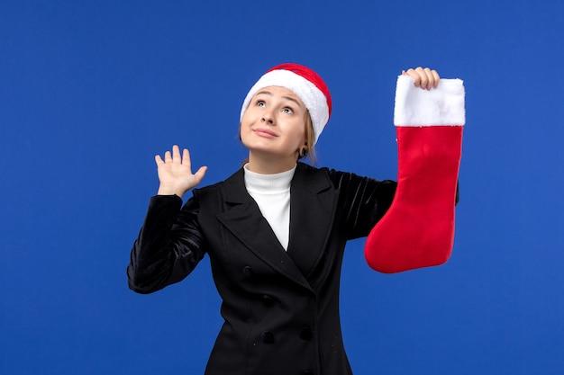 正面図青い壁の人間の休日の新年に赤いクリスマス靴下を保持している若い女性