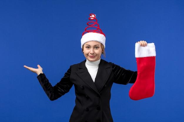 Вид спереди молодая женщина держит красный рождественский носок на синей стене человеческий новогодний праздник