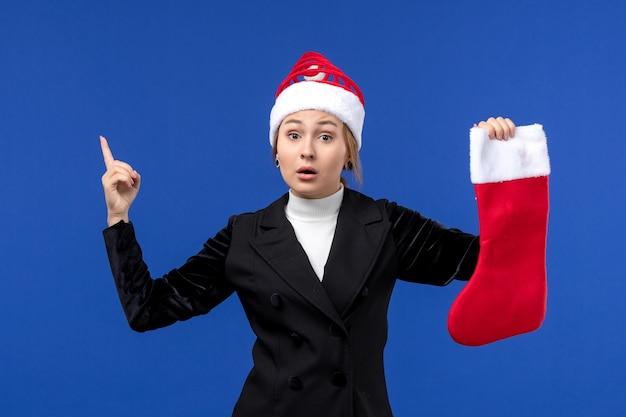 正面図青い壁の人間の新年の休日に赤いクリスマス靴下を保持している若い女性