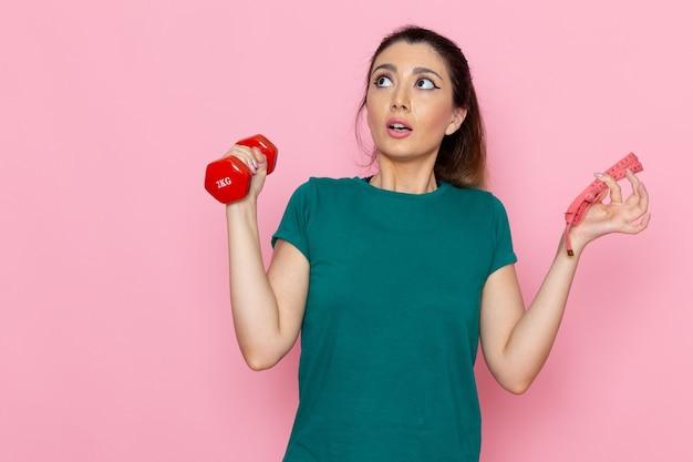 Giovane femmina di vista frontale che tiene i manubri rossi sulla parete rosa chiaro atleta sport esercizio fisico allenamenti