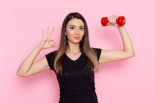 Вид спереди молодая женщина, держащая красные гантели на светло-розовой стене, спортсмен, спортивные упражнения, тренировка для здоровья