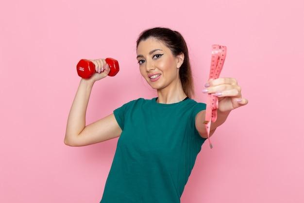 明るいピンクの壁のアスリートスポーツ運動健康トレーニングに赤いダンベルを保持している正面図若い女性