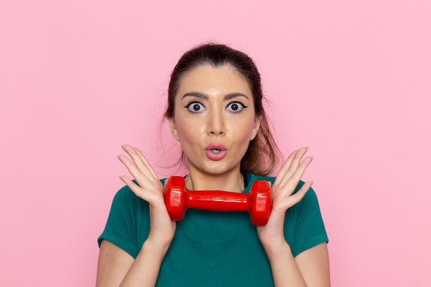 분홍색 벽 선수 스포츠 운동 건강 운동에 빨간색 아령을 들고 전면보기 젊은 여성