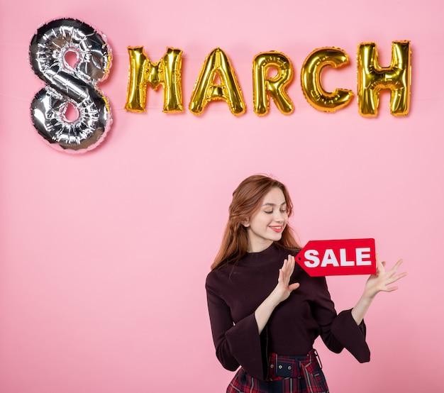 Vista frontale giovane donna con targhetta rossa in vendita su festa di matrimonio rosa festa delle donne regalo vacanza shopping