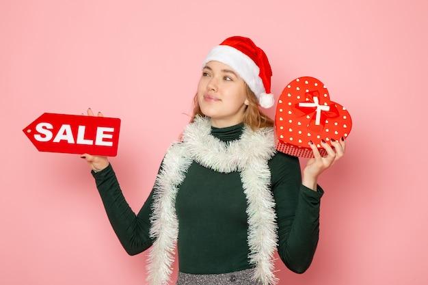 Вид спереди молодая женщина, держащая красную распродажу, пишет и присутствует на розовой стене рождество, новый год, эмоция, праздник