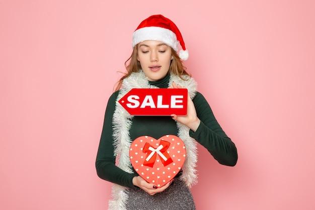 Вид спереди молодая женщина держит красную распродажу, пишет и присутствует на розовой стене рождество, новый год, мода, эмоция, праздник