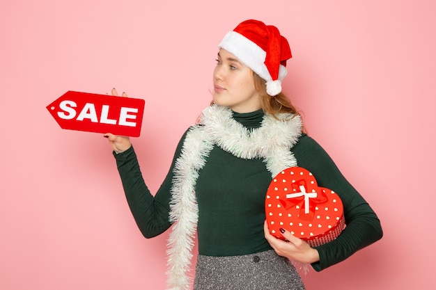 Вид спереди молодая женщина, держащая красную распродажу, написание и подарок на розовой стене, рождество, новый год, шоппинг, эмоция, цвет праздника