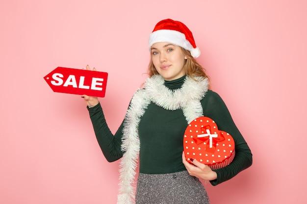 Вид спереди молодая женщина держит красную распродажу, пишет и присутствует на розовой стене, рождество, новый год, шоппинг, эмоции, праздничные цвета