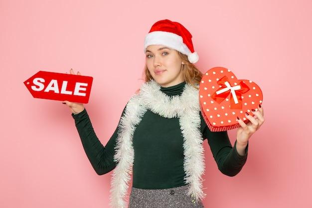 Вид спереди молодая женщина держит красную распродажу, пишет и присутствует на розовой стене, рождество, новый год, шоппинг, эмоция, праздник