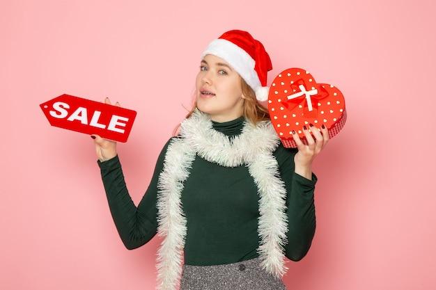 Вид спереди молодая женщина, держащая красную распродажу, написание и подарок на розовой стене, рождество, новый год, шоппинг, эмоция, цвет праздников