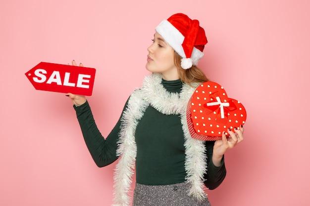 Вид спереди молодая женщина держит красную распродажу, пишет и присутствует на розовой стене, рождество, новый год, шоппинг, эмоции, праздники