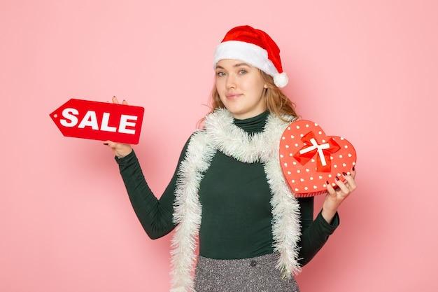 Вид спереди молодая женщина, держащая красную распродажу, пишет и присутствует на розовой стене, рождество, новый год, покупки, мода, эмоция, праздник