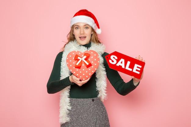 Вид спереди молодая женщина держит красную распродажу, пишет и присутствует на розовой стене, рождество, новый год, покупки, мода, эмоции, праздник