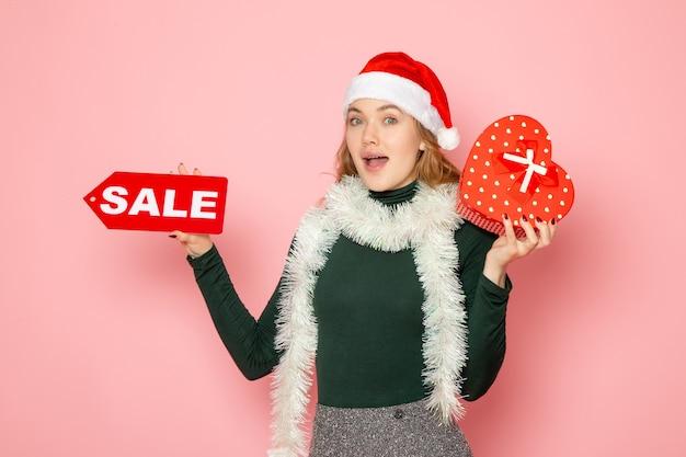 Вид спереди молодая женщина, держащая красную распродажу, пишет и присутствует на розовой стене, новогодняя покупка эмоций