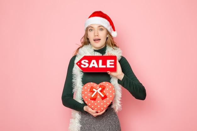 Вид спереди молодая женщина, держащая красную распродажу, пишет и присутствует на розовой стене, новогодняя покупка, модный праздник