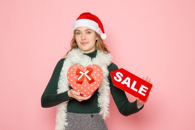 핑크 벽 새 해 쇼핑 패션 감정 휴일에 빨간색 판매 쓰기를 들고 전면보기 젊은 여성