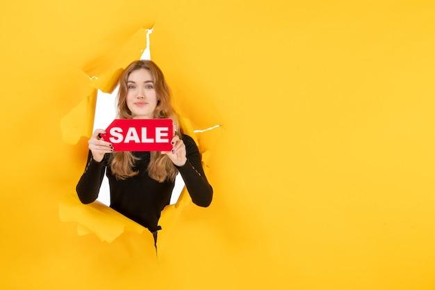 노란색 찢어진 벽에 빨간색 판매 쓰기를 들고 전면보기 젊은 여성