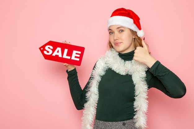 Front view young female holding red sale writing on pink wall christmas new year shopping fashion emotion holidays