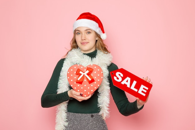 Front view young female holding red sale writing on pink wall new year shopping fashion emotion holiday